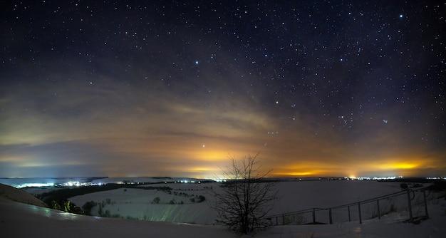 Estrelas do céu noturno com nuvens. paisagem de inverno com neve ao anoitecer