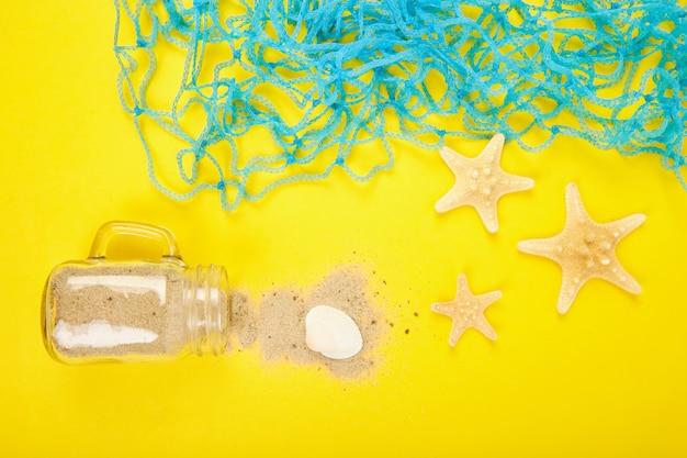 Estrelas do mar e conchas, vidro com areia em fundo amarelo