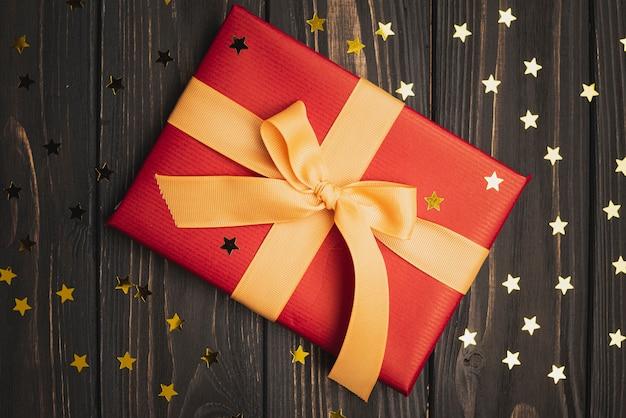 Estrelas douradas e presente de natal em fundo de madeira