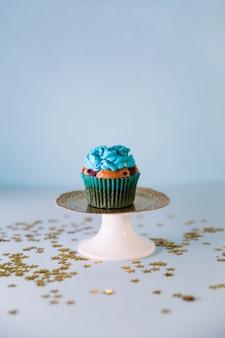 Estrelas douradas espalhadas sobre o fresco e saboroso bolinho de aniversário no cakestand em pano de fundo azul