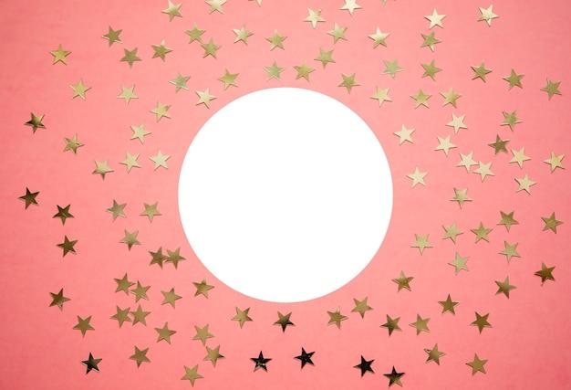 Estrelas douradas holográficas no fundo coral na moda.