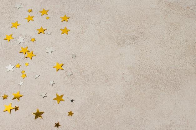 Estrelas festivas de cópia espaço dourado na mesa