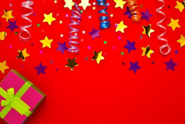 Estrelas festivas douradas e roxas de confete e um presente sobre um fundo vermelho. espaço para texto ou desenho.
