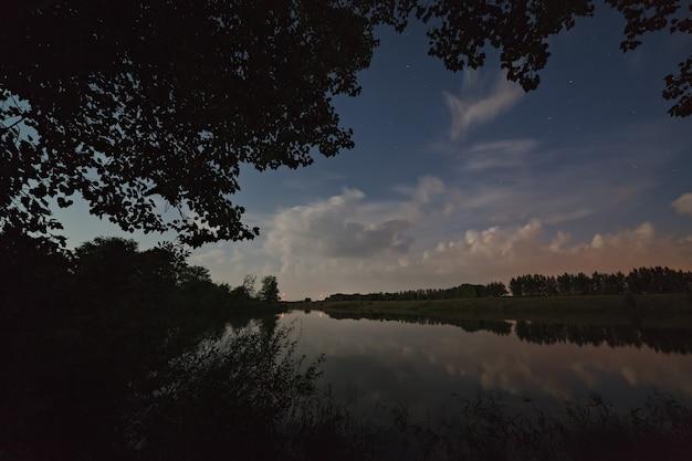 Estrelas no céu com nuvens. paisagem noturna com um lago.