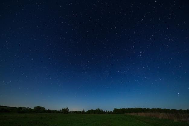 Estrelas no céu noturno com as luzes da cidade no horizonte. a paisagem é fotografada ao luar.