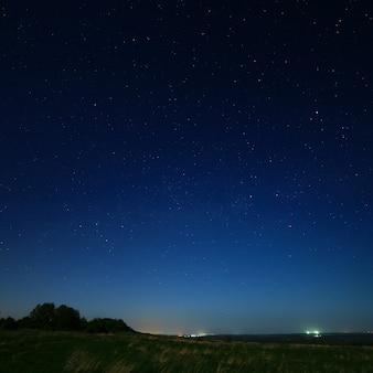 Estrelas no céu noturno com luzes da cidade no horizonte