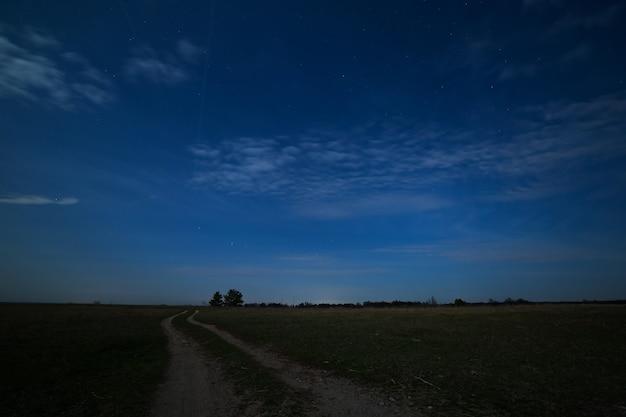Estrelas no céu noturno com nuvens sobre a estrada