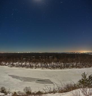 Estrelas no céu noturno. paisagem de inverno com um rio congelado fotografado sob a lua cheia.