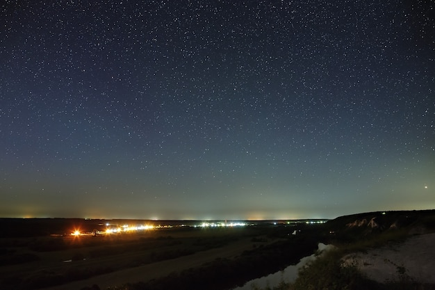 Estrelas no céu noturno, sobre o vale do rio e a cidade. o espaço cósmico é fotografado em uma longa exposição.
