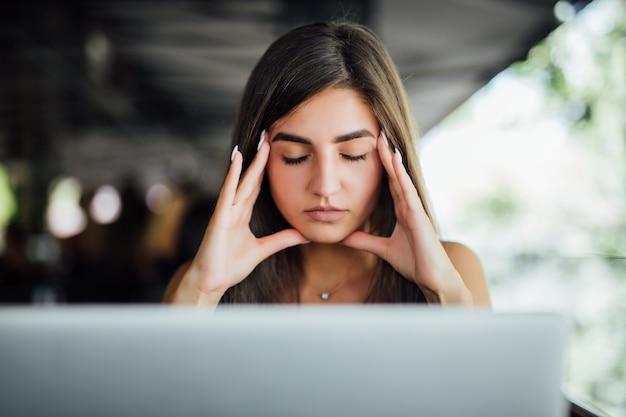 Estressada jovem cansada e ocupada trabalhando em seu relatório na frente do laptop no café de verão
