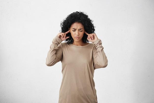 Estressada, jovem mulher de pele escura, frustada, vestindo uma blusa bege de mangas compridas e tampando as orelhas