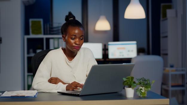 Estressada mulher gerente africana trabalhando com gráficos financeiros, verificando gráficos, digitando no laptop, lendo raports tarde da noite no escritório start-up, fazendo horas extras para respeitar o prazo do projeto.