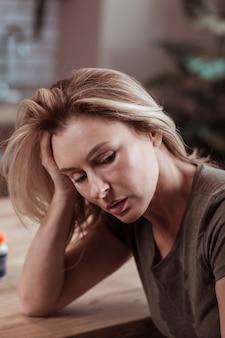 Estressado e doente. perto de uma mulher loira madura vestindo uma camiseta, sentindo-se estressada e doente