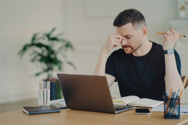 Estressado e pensativo freelancer masculino ou empresário casual sentindo-se cansado e tendo problemas no trabalho enquanto está sentado em sua mesa de trabalho com o laptop no escritório em casa, trabalhador de escritório masculino nervoso