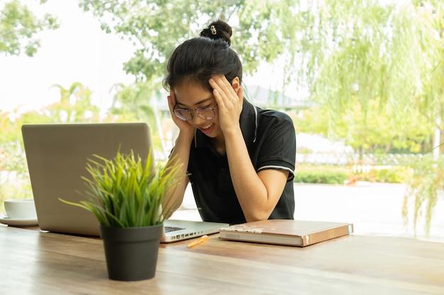 Estressado estudante sentindo dor repentina depois de muito tempo usando o laptop para estudo.