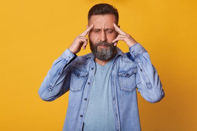 Estressado homem de meia idade frustrado coloca os dedos nas têmporas, sentindo-se mal, tendo dor de cabeça, dores nas têmporas, olhando para o chão, concentrado em seus pensamentos e idéias, sendo ocupado e tenso.