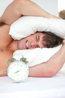 Estressado homem wokenup pelo seu despertador, colocando a cabeça sob o travesseiro
