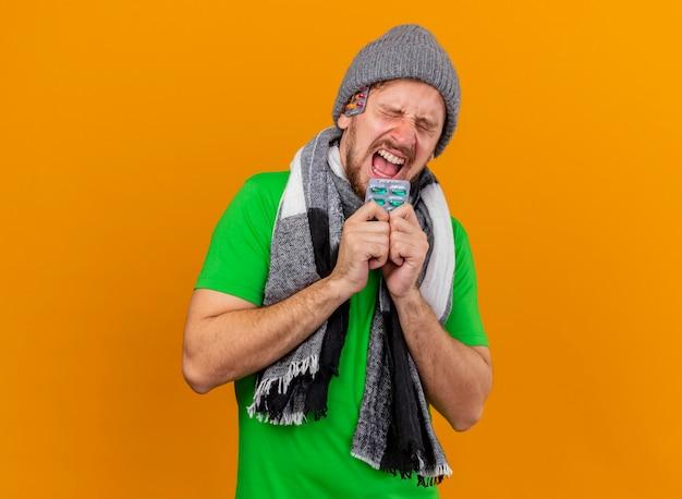 Estressado, jovem, bonito, doente, usando chapéu de inverno e lenço segurando um pacote de cápsulas gritando com os olhos fechados com um pacote de cápsulas sob o chapéu isolado na parede laranja
