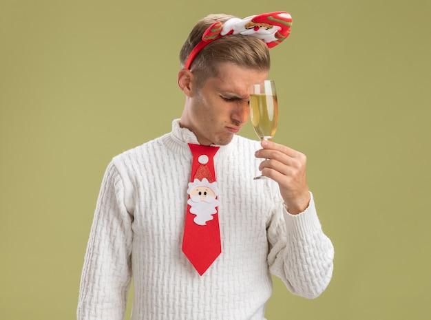 Estressado jovem bonito usando bandana de papai noel e gravata segurando uma taça de champanhe tocando a testa com ela com os olhos fechados, isolada na parede verde oliva com espaço de cópia