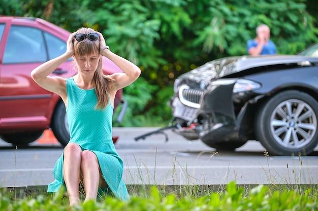 Estressado motorista de mulher sentada na rua chocada após acidente de carro. segurança rodoviária e conceito de seguro.
