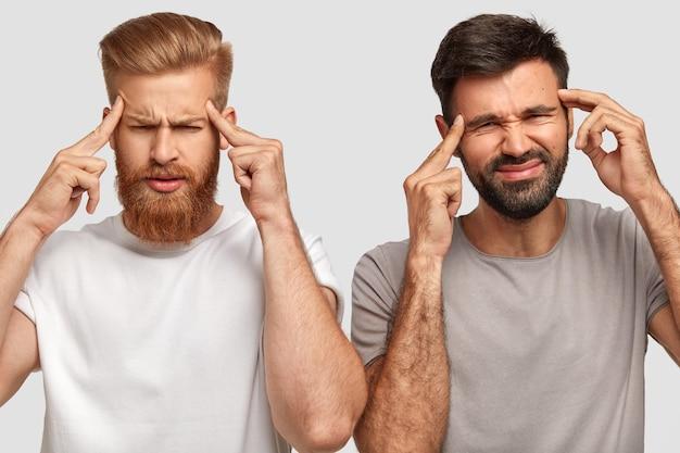 Estressados, dois amigos jovens com a barba por fazer mantêm os dedos da frente nas têmporas e têm expressões deprimidas