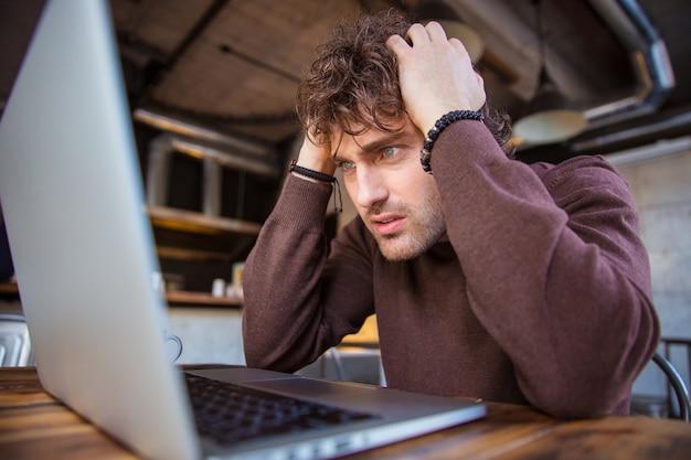 Estressante chateado, desesperado, bonito homem encaracolado com camiseta marrom, trabalhando com laptop e tendo dor de cabeça
