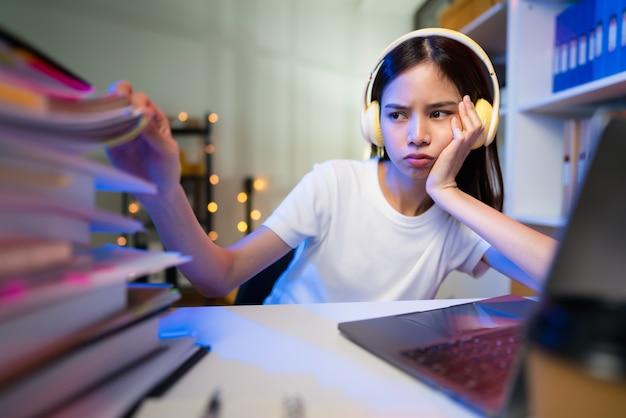 Estressante jovem asiática usando fone de ouvido e sentado na cadeira com uma pilha de documentos em cima da mesa e olhando na tela do computador à noite.
