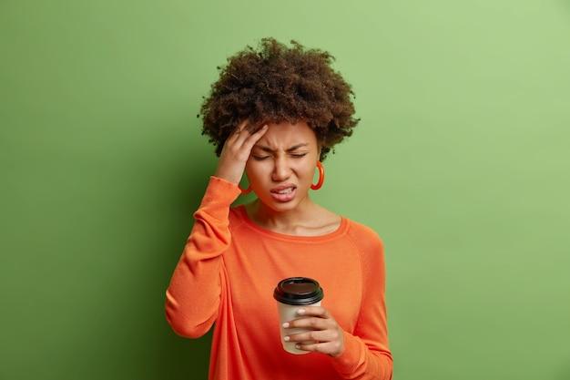 Estressante mulher afro-americana com uma terrível dor de cabeça sorri maliciosamente de dor fecha os olhos, toca o templo, bebe café usa um macacão laranja casual isolado sobre uma parede verde viva