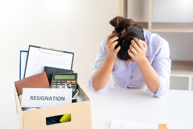Estresse de mulher de negócios embalando uma caixa de papelão marrom que pertencia após pedir demissão