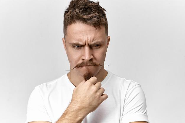 Estresse, problemas e emoções humanas negativas. foto de um jovem bonito e frustrado em uma camiseta branca posando dentro de casa, franzindo a testa e tocando sua barba estilosa, tendo uma aparência preocupada