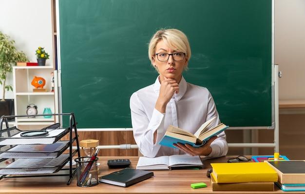 Estrita jovem loira professora de óculos, sentada na mesa com o material escolar na sala de aula, segurando o livro aberto, segurando o queixo, olhando para frente