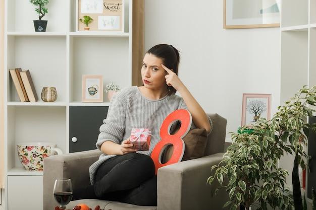 Estritamente colocando o dedo no templo, linda garota no dia da mulher feliz, segurando um presente sentado na poltrona na sala de estar