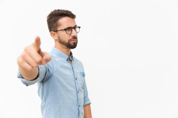 Estrito cara carrancuda no dedo apontando de óculos