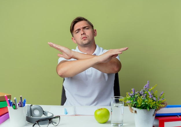 Estrito jovem bonito estudante do sexo masculino sentado na mesa com as ferramentas da escola, mostrando o gesto de não isolado no verde oliva