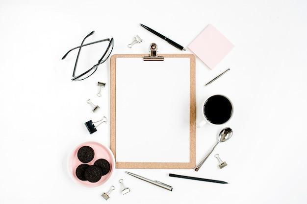Estrutura da mesa do espaço de trabalho do escritório em casa rosa pálido com área de transferência, café, biscoitos, óculos e material de escritório na superfície branca