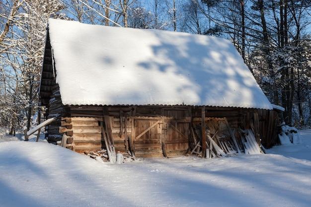 Estrutura de madeira na floresta. usado como celeiro no campo. a foto é tirada em close em um clima ensolarado no inverno. há neve na superfície
