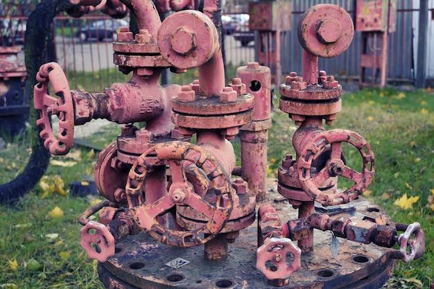 Estrutura de tubulação industrial enferrujada complicada com muitas rodas de tubulação diferentes; foco na roda dianteira