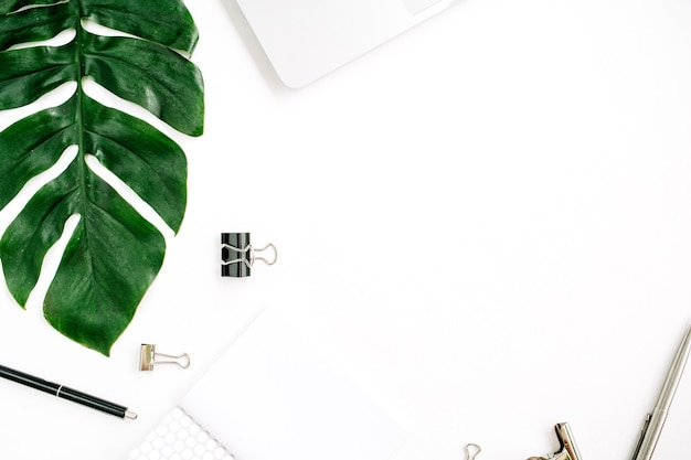 Estrutura do espaço de trabalho de home office com laptop, folha de palmeira e acessórios
