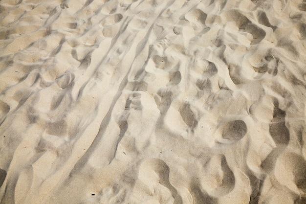 Estrutura irregular ondulada de areia na praia no mar, close-up da areia fina e fofa na costa