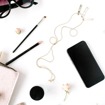 Estrutura plana de mesa de escritório com vista superior. área de trabalho da mesa feminina com embreagem, cosméticos, telefone, óculos de sol, botões de rosa de batom em fundo branco.