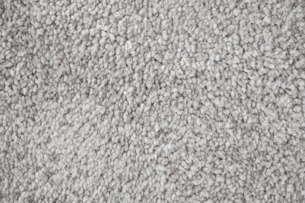 Estrutura têxtil de tapete de banho macio. fim cinzento do tapete acima da foto.