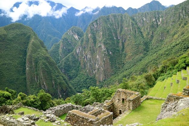 Estruturas antigas e terraços agrícolas na encosta da montanha da cidadela inca de machu picchu, peru