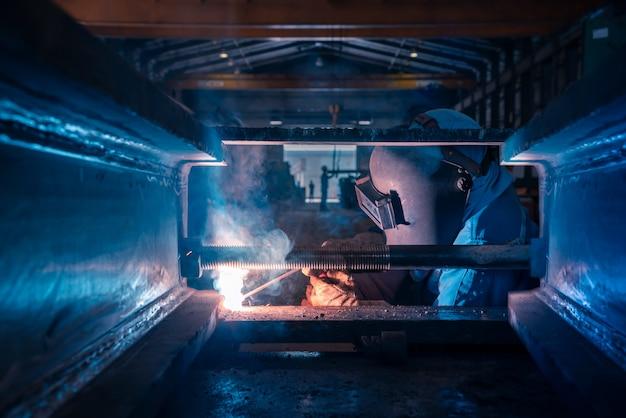 Estruturas de aço de soldagem e faíscas brilhantes na indústria da construção civil. tom azul