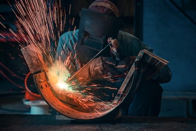 Estruturas de aço para soldagem e faíscas brilhantes na indústria da construção em aço. tom azul