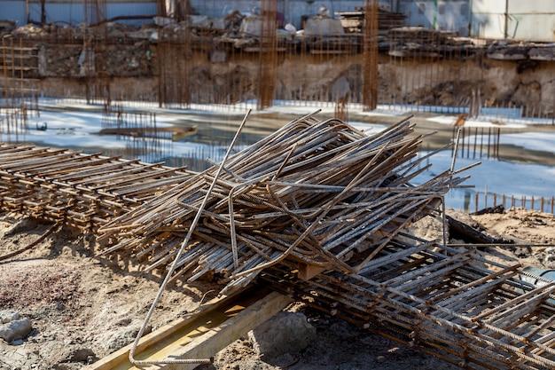 Estruturas metálicas para estruturas de concreto. local de construção, ferramentas, carrinho de mão, areia e tijolos na construção de uma nova casa, máquina misturadora de cimento e acessórios