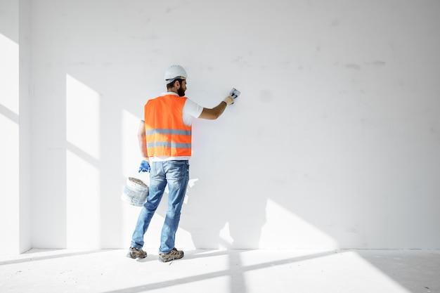 Estucador em vestuário de trabalho, alisando a superfície da parede do edifício dentro de casa