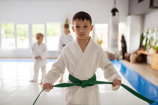 Estudando artes marciais. garoto sério de cabelos escuros estudando arte marcial usando quimono e faixa verde