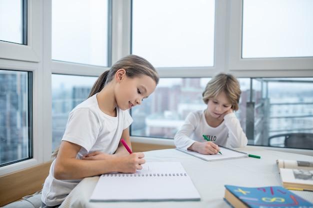 Estudando em casa. irmãos estudando em casa e dando aulas juntos