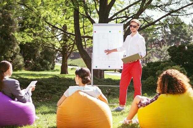 Estudando muito. jovem concentrado em pé perto do quadro e discutindo seu projeto universitário com os amigos