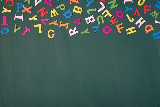 Estudando no conceito de escola. foto de visão aérea superior acima de letras coloridas isoladas em uma lousa com um espaço vazio em branco